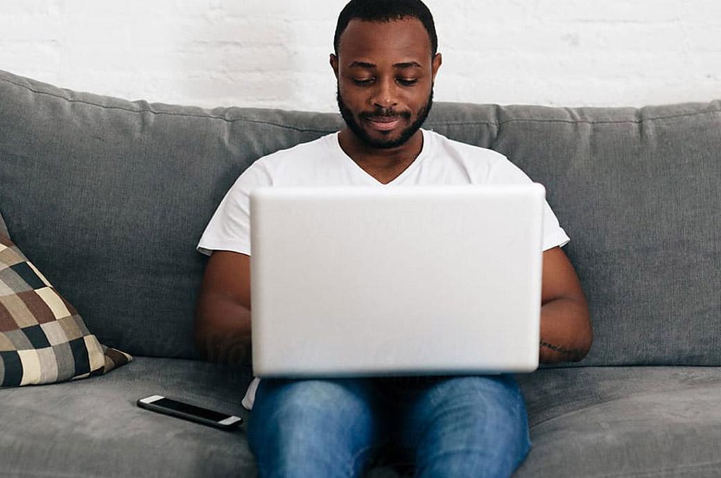 A man sitting on a sofa using a laptop