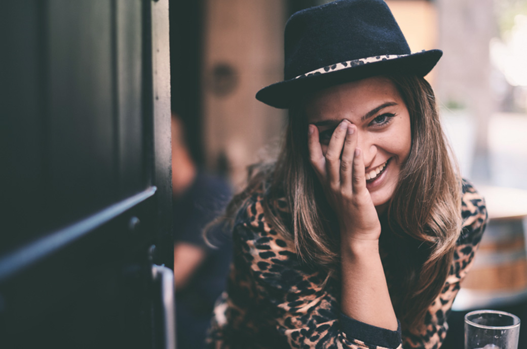 Girl covering her eyes with her hands smiling.